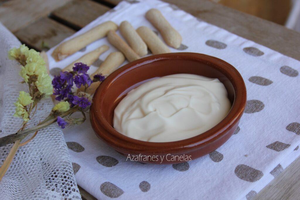 Receta de mayonesa casera clásica: cazuela de barro con mayonesa casera y unos roscos de pan. Un poco de flor de lavanda acompaña a la imagen.